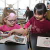 Morey Elementary School students pick out a free book each, ahead of spring break, through Reading is Fundamental. Sophia Andrews, 5, left, and Rachana Momuong, 6, both kindergarten students. (SUN/Julia Malakie)