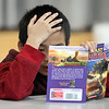 Morey Elementary School students pick out a free book each, ahead of spring break, through Reading is Fundamental. Fourth grader Jayden Yean, 10, starts reading his book. (SUN/Julia Malakie)