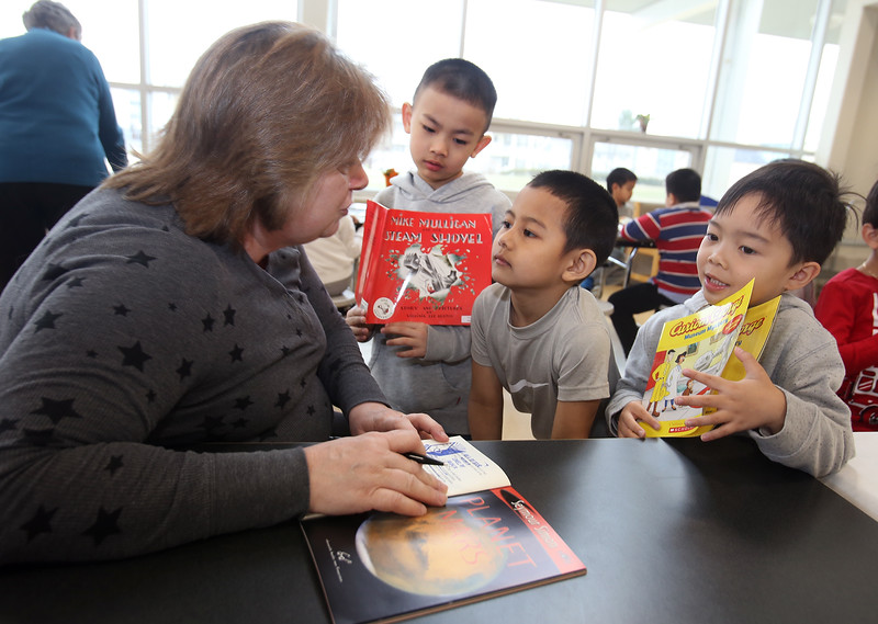 Morey Elementary School students pick out a free book each, ahead of spring break, through Reading is Fundamental. From left, paraprofessional Diane Ducharme of Lowell writes names in books for kindergarten students Panha Sopheak, 6, Soto Sek, 5, and Thomas Heng, 6. (SUN/Julia Malakie)