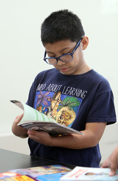 Morey Elementary School students pick out a free book each, ahead of spring break, through Reading is Fundamental. Fourth grader Lucas Cartmel, 10, browses books. (SUN/Julia Malakie)