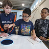 Morey Elementary School students pick out a free book each, ahead of spring break, through Reading is Fundamental. From left, 4th graders Antoine Brennan, 10, Lucas Cartmel, 10, and Xayvian Tembo, 10, stamp the books they picked out. (SUN/Julia Malakie)