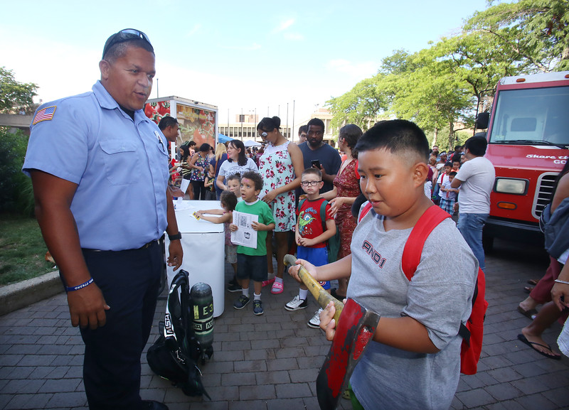 Back-to-school party for Lowell public schools at JFK Plaza. T.J. Tai, 10, of Lowell, who's going into 5th grade, feels how heavy a Lowell Fire Department axe is, after answering some fire safety questions correctly for Lt. Bryant Potter, left. (SUN/Julia Malakie)