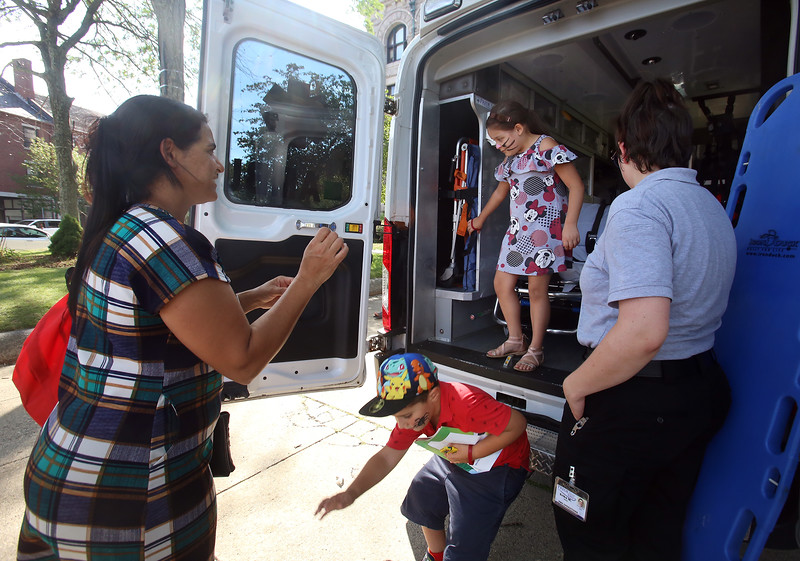 Back-to-school party for Lowell public schools at JFK Plaza. Nalva Freitas of Lowell, left, watches a friend's son Salvador Barbosa, 7, and his friend Livia Freitas, 7 (no relation), jump out of the PrideStar ambulance on display. All are from Lowell. At right is EMT Erika Merrill of Dracut. (SUN/Julia Malakie)