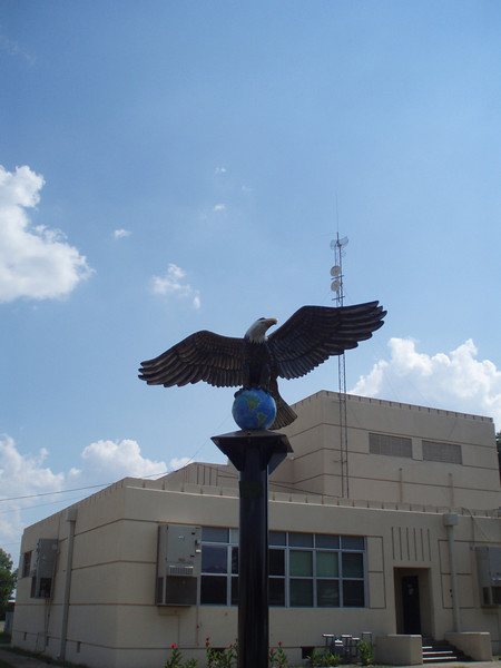Eagle mascot Pole outside of old gym. 6/23/12.<br /> As I examine this image, I believe that my mistake was that I should have taken the picture under the eagle for a full sky background.  As it is maybe Photoshop elements can fill in the sky and the building can be erased.