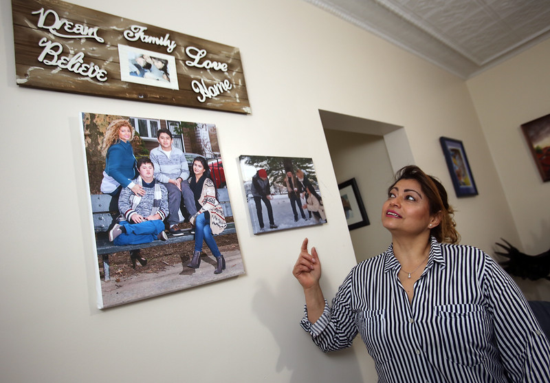 MCC graduate Claudia Aguirre of Lowell, at home, with photos of her three children. In the large photo, Aguirre, top left, sons Luis Enrique Afanador, now 22, who has Down syndrome, bottom left, and Nicolas Afanador, now 17, and daughter Pamela Afanador, now 26, who now lives in NYC.(SUN/Julia Malakie)