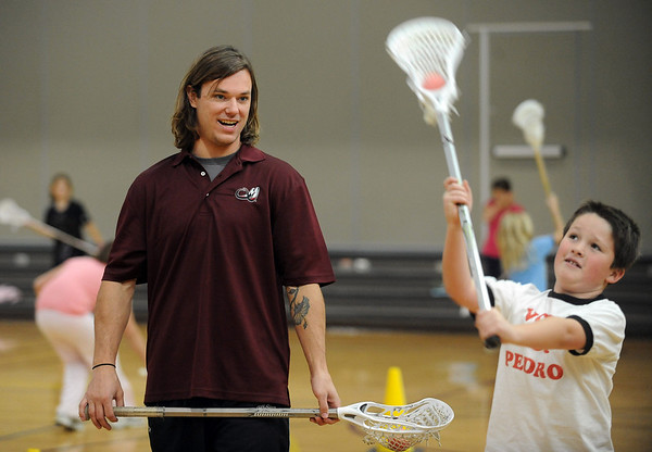 "Jarett Park of the Colorado Mammoth, helps Aidan Jones with his passing form during Doug Dombek's gym class.<br /> Colorado Mammoth lacrosse players teach the game at Louisville Elementary as part of the Stick 4 Schools program.<br />  For more photos and a video, go to  <a href=""http://www.dailycamera.com"">http://www.dailycamera.com</a>.<br /> Cliff Grassmick / November 19, 2010"