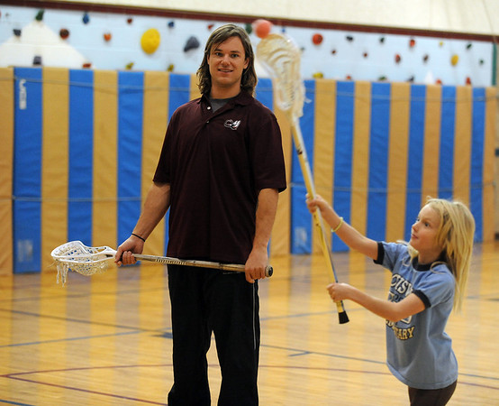 """Jarett Park of the Colorado Mammoth, helps Sasha Snoeck with her passing form during Doug Dombek's gym class.<br /> Colorado Mammoth lacrosse players teach the game at Louisville Elementary as part of the Stick 4 Schools program.<br />  For more photos and a video, go to  <a href=""""http://www.dailycamera.com"""">http://www.dailycamera.com</a>.<br /> Cliff Grassmick / November 19, 2010"""