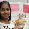McCarthy Middle School's annual Science & Engineering Fair. Fifth grader Freya Shah, 11, of Chelmsford, holds a plastic bag that's holding water despite having pencils pushed through it, part of her project about Polymers. (SUN Julia Malakie)