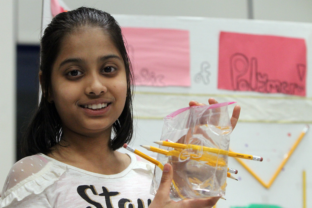 . McCarthy Middle School\'s annual Science & Engineering Fair. Fifth grader Freya Shah, 11, of Chelmsford, holds a plastic bag that\'s holding water despite having pencils pushed through it, part of her project about Polymers. (SUN Julia Malakie)