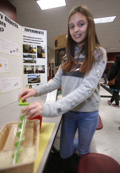 McCarthy Middle School's annual Science & Engineering Fair. Fifth grader Teegan Toto, 10, of Chelmsford, uses an Archimedes Screw to move grains of rice, part of her project, How Were Heavy Objects Moved Before Electricity? (SUN Julia Malakie)