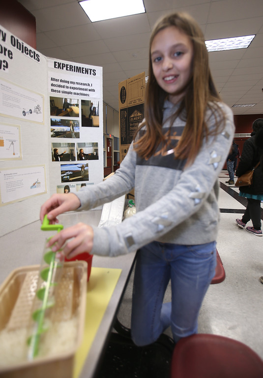 . McCarthy Middle School\'s annual Science & Engineering Fair. Fifth grader Teegan Toto, 10, of Chelmsford, uses an Archimedes Screw to move grains of rice, part of her project, How Were Heavy Objects Moved Before Electricity? (SUN Julia Malakie)