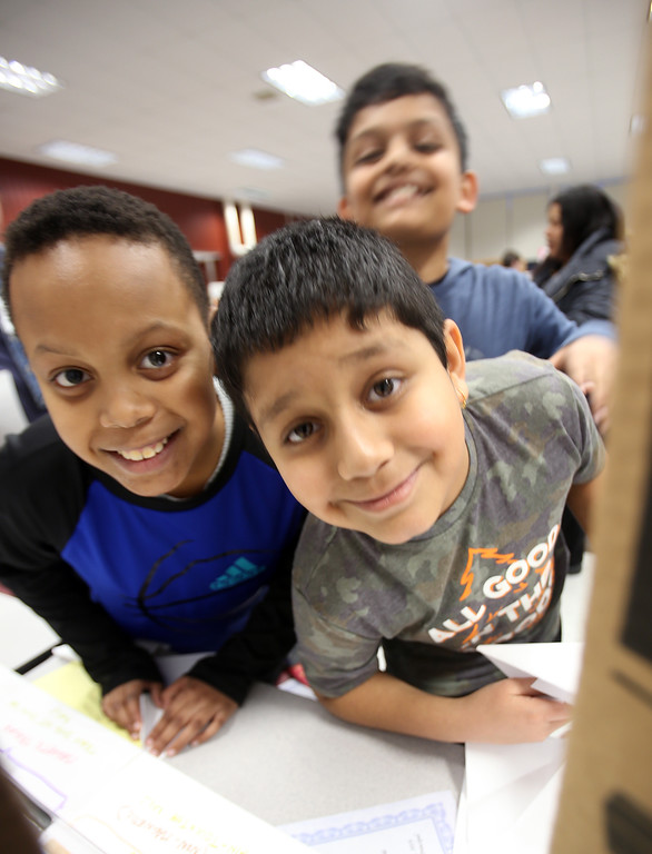 . McCarthy Middle School\'s annual Science & Engineering Fair. Fifth graders Jayden Hector-Davis, left, Agastya Bhatlapenumarthy, right, and Ayaan Srivastava, rear, all 10, peer between displays. They did a project on a Maglev Train, and were making paper airplanes at the next exhibit. (SUN Julia Malakie)
