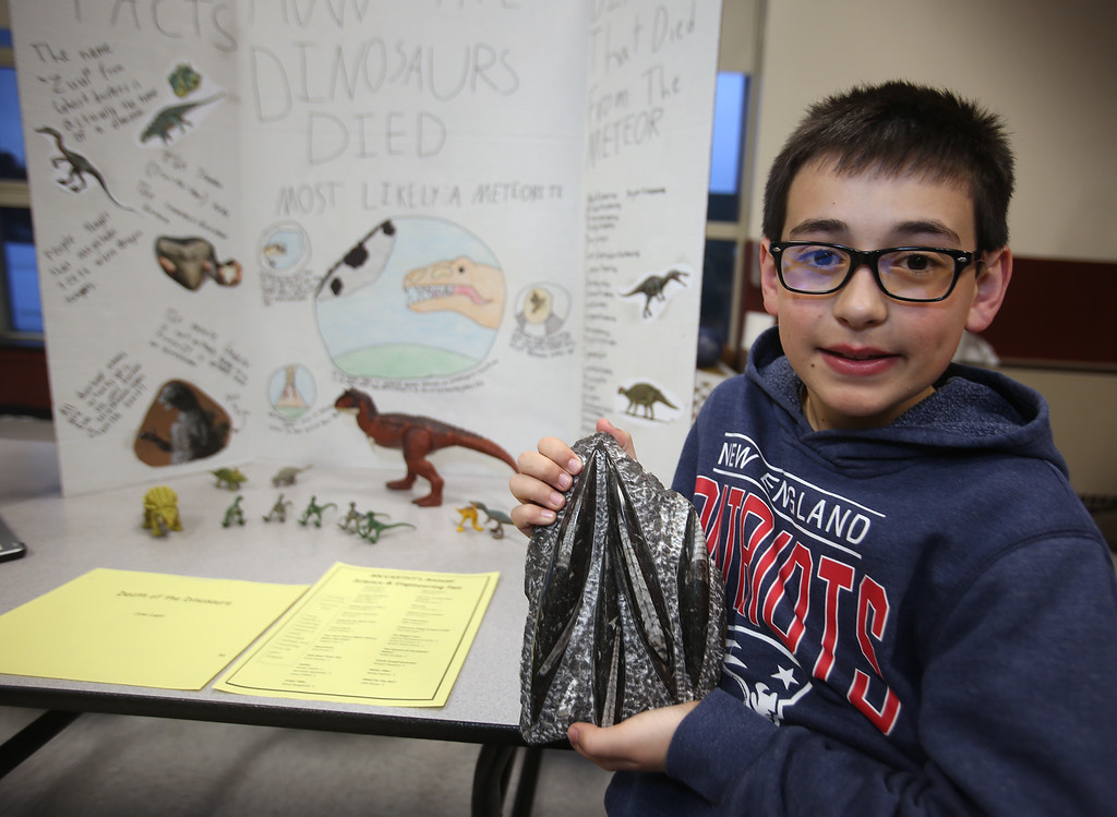 . McCarthy Middle School\'s annual Science & Engineering Fair. Fifth grader Jake Leger, 11, of Chelmsford, with his exhibit, How the Dinosaurs Died, about the Cretaceous Period. He\'s holding an orthoceras fossil that someone gave him. Orthoceras was a squid-like mollusk. (SUN Julia Malakie)