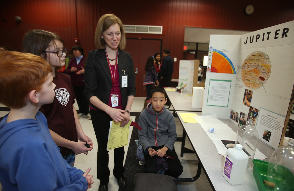 . McCarthy Middle School\'s annual Science & Engineering Fair. Fifth graders from left, LIam O\'Neill, Kennedy Apostolou, and Austin Haack, all 11, talk to Pam O\'Meara, a 7th & 8th grade tech engineering, about their project on Jupiter. (SUN Julia Malakie)