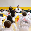 Instructor Jihoon Kim of the Leominster U.S. Taekwondo Center leads a group of McKay Arts Academy 3rd graders during a Taekwondo demonstration for family and friends during their graduation from the 8-week class, Monday night in Fitchburg.<br /> SENTINEL & ENTERPRISE / BRETT CRAWFORD