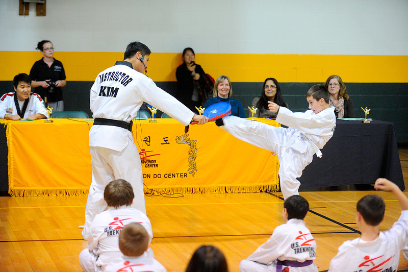 McKay Arts Academy 3rd grader Ian Tassos, 9, performs a kick with Instructor Jihoon Kim of the Leominster U.S. Taekwondo Center during a Taekwondo demonstration for family and friends during the group's graduation from an 8-week class, Monday night in Fitchburg.<br /> SENTINEL & ENTERPRISE / BRETT CRAWFORD