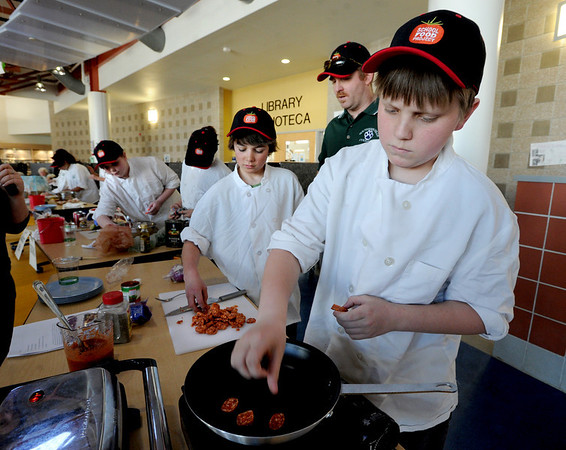 "Johannes Thomas-Larsen, right, of the Southern Hills team, cooks up some sausage for his team.<br /> Area middle schools competed in an Iron Chef- style competition at Casey Middle School in Boulder on Thursday. The winning school will win money for the school and have their recipe used for school lunches.<br /> For a video and photos of the competition. go to  <a href=""http://www.dailycamera.com"">http://www.dailycamera.com</a>.<br /> Cliff Grassmick / March 22, 2012"