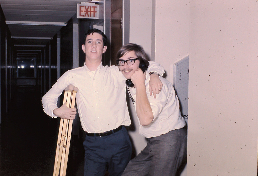 Unknown Student with Crutches on left side of photograph; Donnie Oaks on right side of photograph, holding telephone.