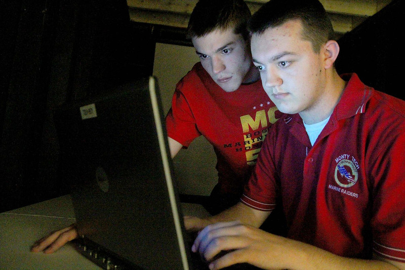 Jack Marabello and Connor Quick, two Monty Tech students who placed ninth and second, respectively, in the governor's Cyber Aces competition are lit up by a laptop on Monday at the school after talking about the competition. SENTINEL & ENTERPRISE/JOHN LOVE