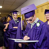 Jacob Gagnon signs a yearbook while waiting for the start of the 45th commencement ceremony held at Monty Tech on Wednesday evening. SENTINEL & ENTERPRISE / Ashley Green