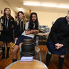 Students work on projects in the middle school STEAM classroom at Notre Dame Academy. From left, 6th graders Rani Bhagat, 12, of Tyngsboro, Genevieve Foy, 11, of Amherst, N.H., Elizabeth Beauregard, 11, of Lowell, Neha Kachappilly, 11, of Nashua, and Isabelle Andrews, 11, of Atkinson, N.H., watch as weights are added to Kachappilly and Andrews' bridge.  The project was to build a bridge with no more than 150 sticks, and see how much weight it could support. (SUN/Julia Malakie)