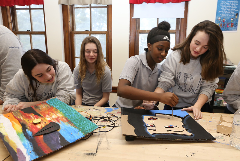"""Students work on projects in the middle school STEAM classroom at Notre Dame Academy. From left, 8th graders Ava Conroy, 14, of Lowell, and Molly Shanahan, 14, of Dunstable, watch Jessica Maina, 13, of Haverhill, and Sophia Creegan, 13, of Lowell work on their version of Roy Lichtenstein's """"Crying Girl."""" The project was programming moving parts and lights into a famous work of art. (SUN/Julia Malakie)"""