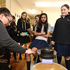 Students work on projects in the middle school STEAM classroom at Notre Dame Academy. From left, STEAM teacher Allison Flynn of Loudon, N.H., left, adds weight to a bridge as 6th graders Rani Bhagat, 12, of Tyngsboro, Genevieve Foy, 11, of Amherst, N.H., Elizabeth Beauregard, 11, of Lowell, Neha Kachappilly, 11, of Nashua, and Isabelle Andrews, 11, of Atkinson, N.H., look on.  The project was to build a bridge with no more than 150 sticks, and see how much weight it could support. (SUN/Julia Malakie)