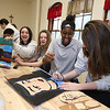 """Students work on projects in the middle school STEAM classroom at Notre Dame Academy. From left, 8th graders Ava Conroy, 14, of Lowell, and Molly Shanahan, 14, of Dunstable, Jessica Maina, 13, of Haverhill, and Sophia Creegan, 13, of Lowell, working on a version of Roy Lichtenstein's """"Crying Girl."""" The project was programming moving parts and lights into a famous work of art. (SUN/Julia Malakie)"""