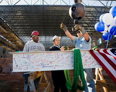 Colombus School Sixth-grader Giovanni Preciado helps ironworkers Juan Villanueva and Craig Klepinger hoist the beam for the Topping Off ceremony Wednesday, September 19th.