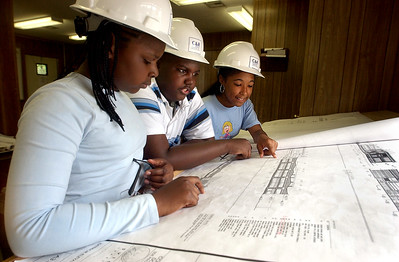 Beecher Construction #3:  Beecher school students Latricia DeRoche,   Frank Hockaday and Tiana Scales look over the blueprints for their new school during a visit to the construction site.