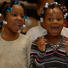 Destiny Short (L) and Cionna, Wilson both 1st graders, sing a song at the Davis school Town Meeting.