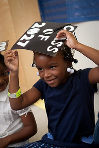 Clarence Rogers kindergartener Maleka Long tries on her 2027 mortar board during a special event on the first day of classes to encourage students to go to college.