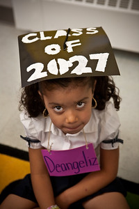 Clarence Rogers kindergartener Deangeliz Melendez tries on her 2027 mortar board during a special event on the first day of classes to encourage students to go to college.
