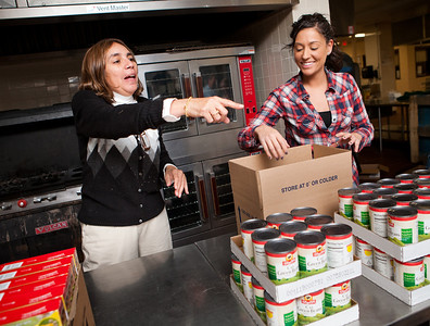 NHPS Chief of Staff Leida Pacini works with volunteer Heather Chasse to pack holiday food donations for needy families.