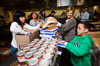 Volunteers from AFB pack holiday food donations for needy families. L-R:  Angie Rodriguez, Elizabeth Delgado, Chris Barbarotta and her grandson Tate.
