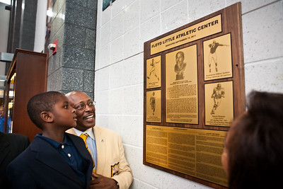 Floyd Little shows his grandson the newly unveiled plaque naming the New Haven Athletic Center the new Floyd Little Athletic Center.