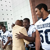 Floyd Little greets Willy Harris and other Hillhouse players during the dedication of the new Floyd Little Athletic Center in New Haven.