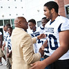 Floyd Little greets Khamil Rangolam and other Hillhouse players during the dedication of the new Floyd Little Athletic Center in New Haven.