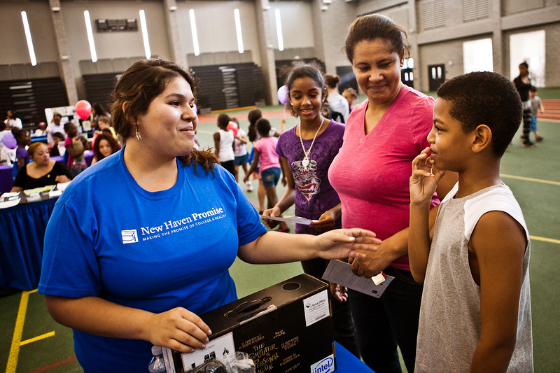 Danielle Guillen of new Haven Promise speaks to Faithlyn Hendricks and her son Duane Hendricks, a student at Troup.