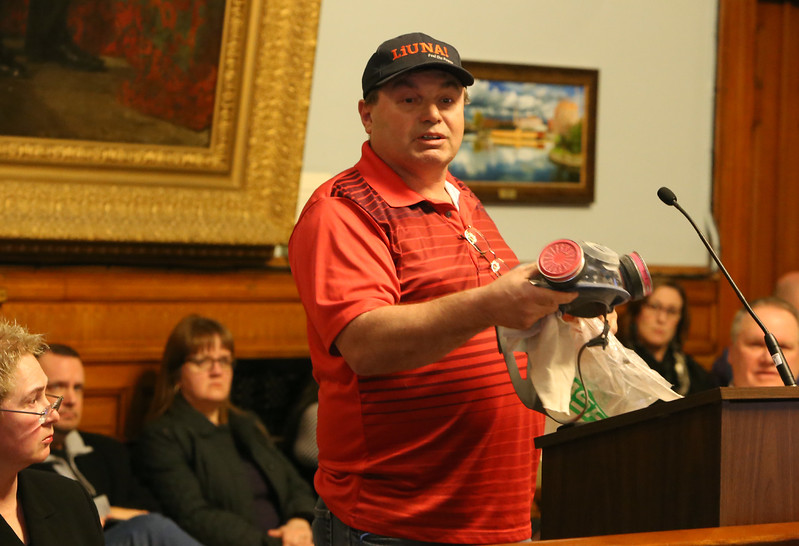 Public forum on plans to renovate or build a new Lowell High School, before City Council vote on whether to narrow down to the recommended four options. Armand Hebert pulls out a safety mask to illustrate his point that a full renovation would encounter asbestos and silica. (SUN/Julia Malakie)