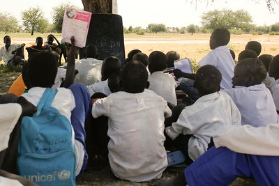 students of Juong Primary school sitting in their classroom under a tree