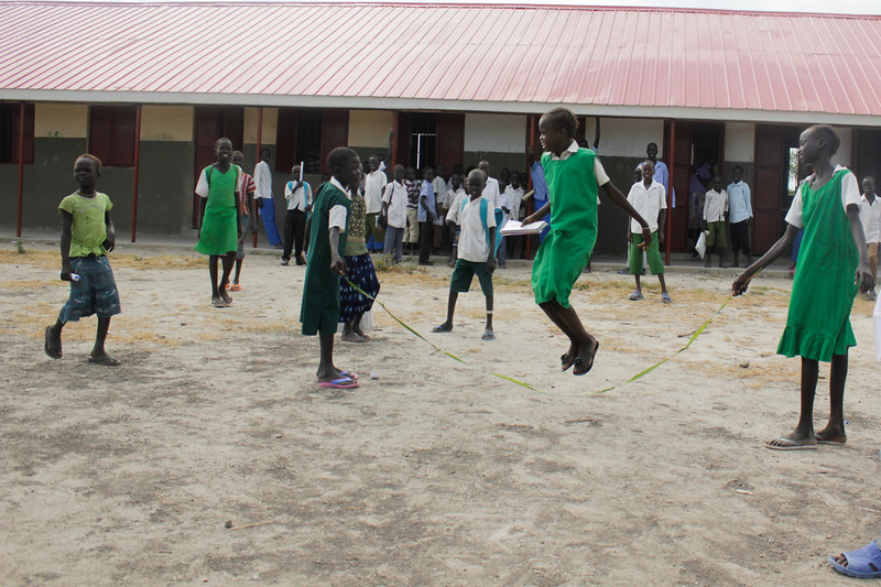 students in Juong Primary school playing skipping rope in front of their new classroom