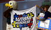 """Bob Raines--Montgomery Media / """"Swoop,"""" the Eagles mascot, helps hold the flag given to Inglewood Elementary School, Lansdale, May 22, 2015 by Patti Erickson, center, president of the Autism Society of Philadelphia, to thank the children for their efforts raising money for autism awareness."""