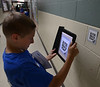 Bob Raines--Montgomery Media / Josh Mascio photographs a QR code containing information on autism scattered along hallways at Inglewood Elementary School May 22, 2015 as part of an autism scavenger hunt.