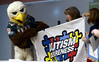 """""""Swoop,"""" the Eagles mascot, helps hold the flag given to Inglewood Elementary School, Lansdale, May 22, 2015 by Patti Erickson, center, president of the Autism Society of Philadelphia, to thank the children for their efforts raising money for autism awareness."""