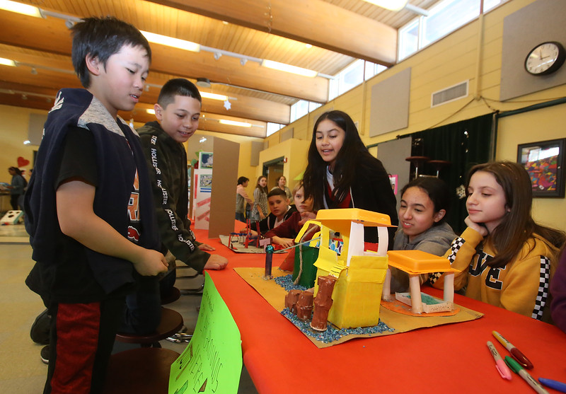 Pyne Arts Magnet School 6th grade geography students learn about playground design from Craig Miller, president of Waterfield Design Group, before holding a Haiti cultural fair/fundraiser in the cafeteria. From left, Bill Qin and Ethan Hernandez look at a model playground made by several students including Anastasia Aponte, Jazmin Sa and Tasia Orphanos. (SUN Julia Malakie)