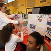Pyne Arts Magnet School 6th grade geography students learn about playground design from Craig Miller, president of Waterfield Design Group, before holding a Haiti cultural fair/fundraiser in the cafeteria. From left, Xiana Rodriguez, Yeleidy Cruz, and Sackaecidy Chamroeun. (SUN Julia Malakie)