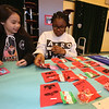 Pyne Arts Magnet School 6th grade geography students learn about playground design from Craig Miller, president of Waterfield Design Group, before holding a Haiti cultural fair/fundraiser in the cafeteria. Samantha Bartlett, left, and Taliya Ligon, arranging her lollypops. (SUN Julia Malakie)
