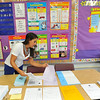 West Side Elementary third grade teacher Sheena Selapack prepares folders for the kids' arrival on Monday, Aug. 26, 2013.