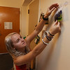 Brianna Langlois, 19, of Westford, hanging up photos in her dorm room, is in UML and MCC's Reserve Placement Progam, spending her first semester at MCC but living at the ICC dorm before becoming a UML student second semester. (SUN/Julia Malakie)